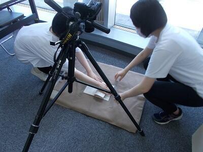 写真:収蔵資料の写真撮影をする実習生の様子