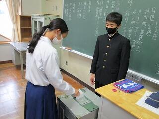 投票箱に入れて終了です 選挙管理委員の生徒がしっかりと見届けています